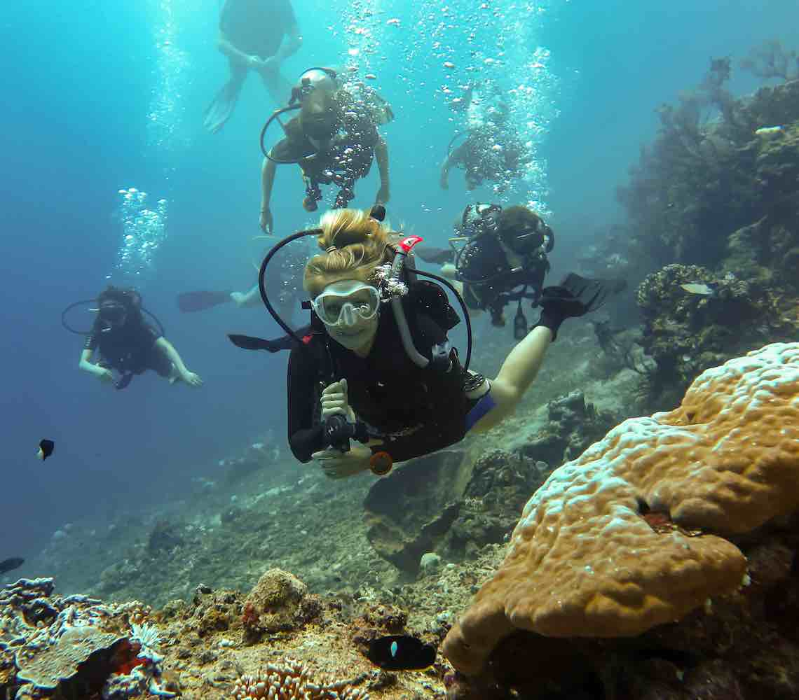 An dive guide gives a smile for the camera as divers follow.